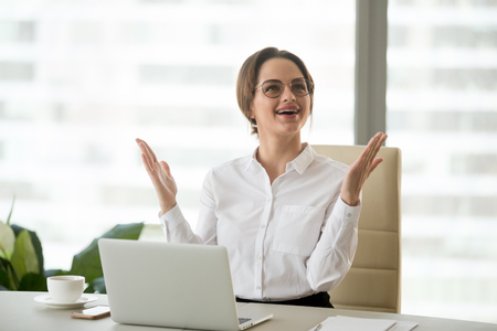 Excited businesswoman raising hands amazed or happy with great news, grateful for business success, online win, impressive achievement, found surprising easy corporate solution or got new good idea Stock Photo
