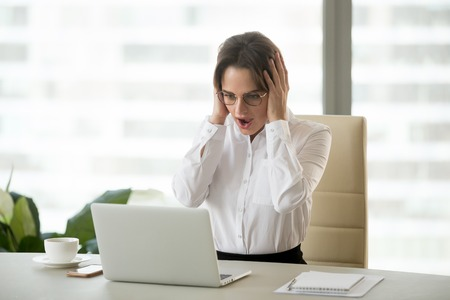 Amazed excited businesswoman shocked with unexpected win online, surprised woman feeling astonished looking at laptop screen with wow face wondering unbelievable email offer, stunned by great news Archivio Fotografico