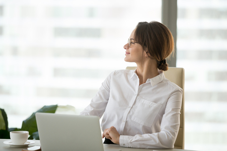 Happy satisfied businesswoman looking away enjoying business success working in office, smiling successful woman boss planning thinking of future goals feeling hopeful motivated about good new job Stock Photo