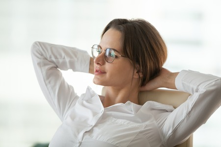 Happy relaxed businesswoman office employee taking break to rest from work holding hands behind head feeling no stress free, planning thinking dreaming of future goals, enjoying wellbeing success Stockfoto