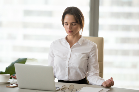 Mindful millennial woman taking break for relaxation meditating in office to reduce work tension, calm successful businesswoman doing yoga exercises feeling zen enjoying no stress free relief concept Stockfoto