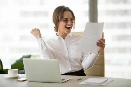 Aufgeregte zufriedene Geschäftsfrau, die Geschäftserfolg feiert, motiviert durch große finanzielle Arbeit, Ergebnis in Bericht, fröhlichem Mitarbeiter, der Brief liest oder Kündigung mit guten Nachrichten glücklich über Jobförderung Standard-Bild