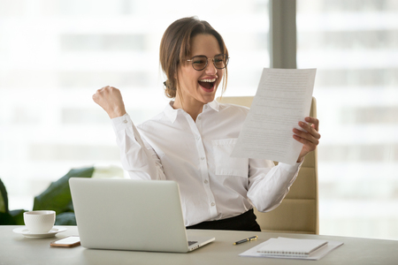 Excited satisfied businesswoman celebrating business success motivated by great financial work result in report, cheerful employee reading letter or notice with good news happy about job promotion Фото со стока - 107343471