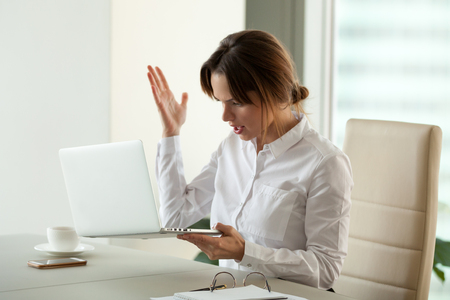 Furious mad businesswoman holding stuck laptop feels angry about bad news online, data loss or software failure, frustrated office worker has problem with pc, stressed employee hates computer crash