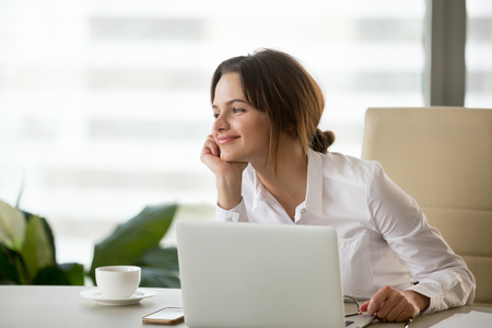 Happy businesswoman looking away satisfied with good new job enjoying business success and wellbeing working in office, smiling woman boss feeling motivated dreaming thinking about future goals