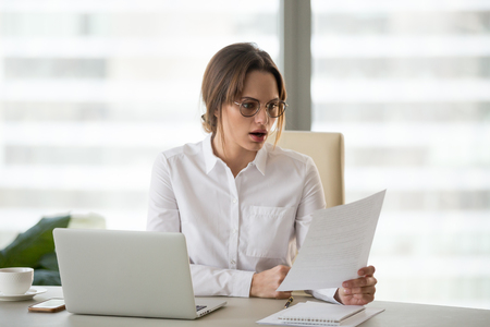 Shocked astonished businesswoman surprised by reading unexpected news in document, amazed woman office worker feeling stunned baffled by unbelievable information in paper about debt or dismissal Archivio Fotografico