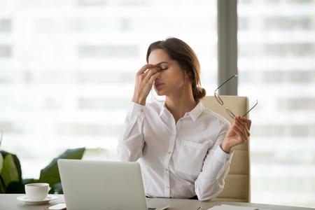 Empresaria fatigada quitándose las gafas cansada del trabajo con la computadora, empleado agotado que sufre de síntomas de visión borrosa después de un uso prolongado de la computadora portátil, mujer con exceso de trabajo siente un problema de tensión ocular