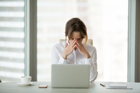 Gefrustreerde zakenvrouw voelt paniekschok na een zakelijke mislukking of slecht nieuws online zittend op kantoor met laptop, gestrest boos vrouwelijke werknemer bezorgd over faillissement, uitgeput moe van overwerk