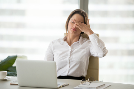 Fatigued businesswoman tired of computer work, female office worker feels dizzy from lack of sleep, headache, hormonal imbalance, eye strain tension, exhausted after long laptop use, overwork concept Stock Photo