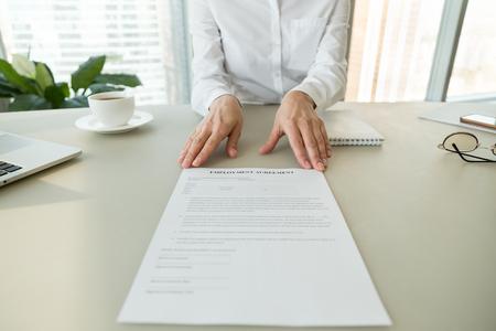 Vrouwelijke hr of werkgever die een arbeidsovereenkomst document aanbiedt voor het lezen van arbeidsvoorwaarden en arbeidsvoorwaarden, het aannemen van een nieuw werknemersproces en het krijgen van een baan, wervingsconcept, close-up