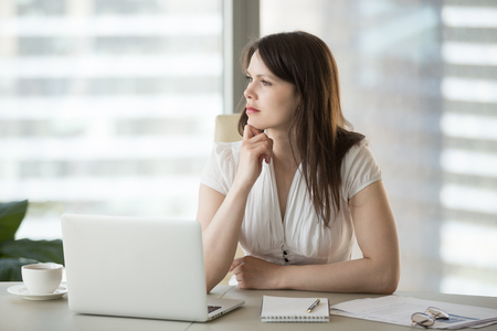 Thoughtful doubtful businesswoman looking away contemplating thinking of problem solution, serious uncertain employee unsure about difficult question deciding planning searching new ideas at work Stock Photo