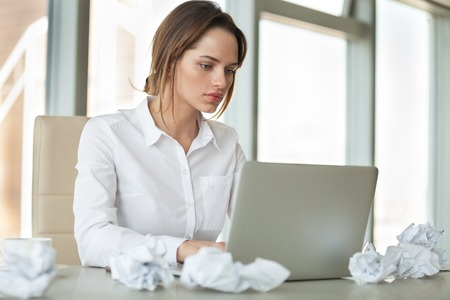 Focused businesswoman preparing report typing on laptop at office desk covered with crumpled paper working hard to finish urgent task, serious writer having block searching new creative ideas online Stock Photo - 107344075
