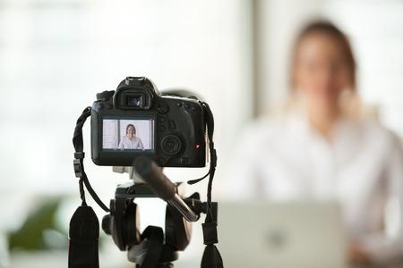 Fotocamera digitale dslr professionale che riprende video blog intervista in diretta o vlog di coach donna vlogger che impartisce lezioni di business o presentazioni formando persone online, realizzando videoblog e concetto di vlogging
