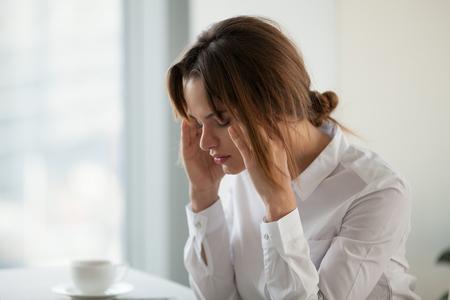 疲れた疲れたビジネスウーマンは、マッサージ寺院に触れる仕事で強い頭痛片頭痛を持ち、めまいや疲労を感じ、オフィスで不安やパニック発作に苦しむ過労の女性を強調しました 写真素材 - 107344083