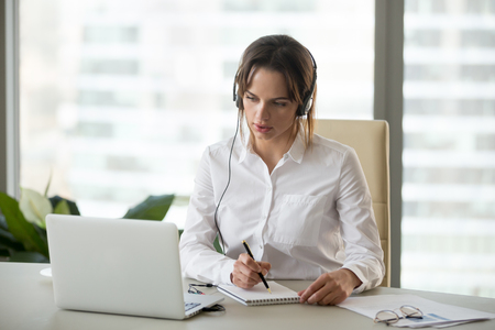 Femme d'affaires sérieuse dans les écouteurs en regardant un webinaire sur un ordinateur portable en prenant des notes, en apprenant à étudier un cours d'informatique, en passant un appel, en participant à une conférence en ligne, en traduisant un cours de formation