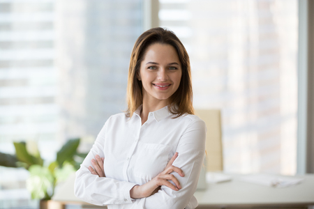 Smiling confident businesswoman looking at camera in office, happy young female ceo, secretary or successful business owner portrait, successful entrepreneur or young professional manager headshot 写真素材