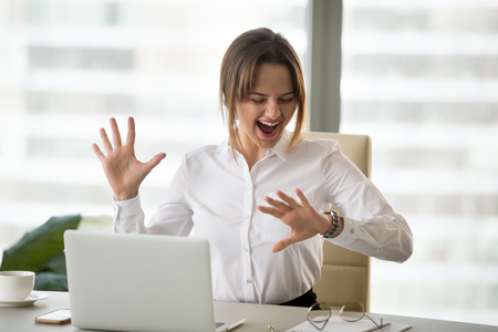 Excited happy employee looking at wristwatch satisfied with meeting deadline finished work day in time, cheerful businesswoman checking time feeling motivated waiting for leaving office on friday