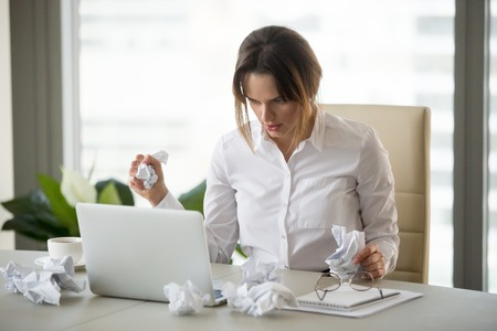 Frustrated stressed businesswoman holding crumpled paper looking at laptop trying to finish urgent work till deadline, disorganized woman writer lost concentration feeling lack of creative ideas Stock Photo - 107344121
