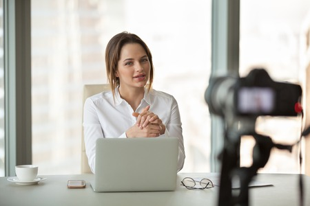 Young businesswoman recording vlog talking to camera in office, successful female business trainer coach filming live video blog giving presentation speaking about online training, vlogging concept Stock Photo