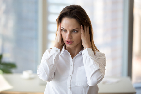 Stressed tired businesswoman in panic feeling fatigued frustrated, exhausted female employee or office worker suffering from overwork, headache, hormone imbalance, having migraine at work concept