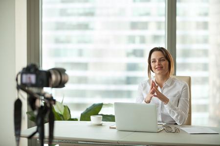 Zelfverzekerde gerichte zakenvrouw vlogger praten met camera filmen live business vlog concept, vriendelijke vrouwelijke coach reclame online opleiding spreken over succes opnemen videoblog in kantoor Stockfoto