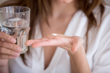 Woman holding pill and glass of water in hands taking emergency medicine, supplements or antibiotic antidepressant painkiller medication to relieve pain, meds side effects concept, close up view Stockfoto