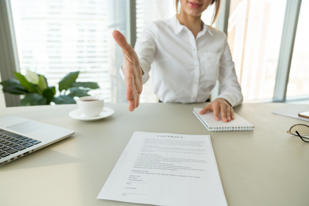 Businesswoman employer extends hand for handshake offers to sign employment contract hiring welcoming congratulating partner promising new job, making bank loan insurance deal concept, close up view