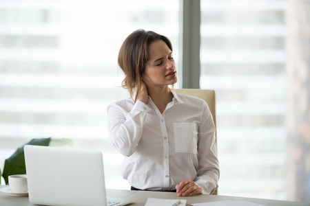 Tired businesswoman feels fatigue massaging tensed muscles of stiff neck trying to relieve pain after sedentary computer work in incorrect posture or uncomfortable office chair, fibromyalgia concept Stock Photo
