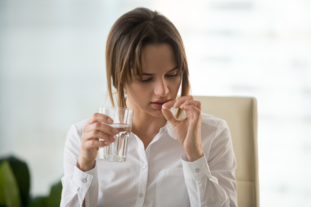 Young woman taking pill to relieve headache or ilness symptoms, stressed businesswoman holding antidepressant or painkiller medication and glass of water, meds for fast pain relief at work concept Stock Photo