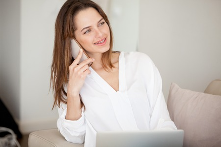 Happy millennial woman talking on the phone at home, smiling young lady holding cellphone making or answering call, beautiful lady speaking by mobile chatting having conversation with friend Stock Photo