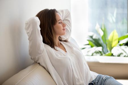 Mujer tranquila relajada descansando respirando aire fresco sintiendo equilibrio mental disfrutando del bienestar en casa en el sofá, joven satisfecha disfrutando de la mañana de fin de semana libre de estrés estirándose en el sofá Foto de archivo - 107344254