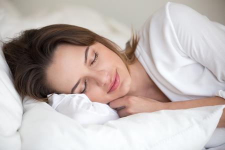 Junge Frau mit schönem Gesicht, das gut auf weißen Baumwolltüchern und weichem Kissen schläft, das schlafend in bequemem gemütlichem Bett zu Hause oder im Hotel liegt und gesundes Nickerchen genießt, das genug für gute Entspannung ruht.