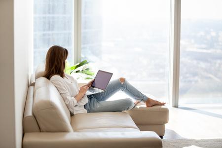 Entspannte Frau, die Laptop im Luxuswohnzimmer mit großem Fenster verwendet, genießt das Arbeiten, das Einkaufen im Internet, das Überprüfen des sozialen Netzwerks, das Lesen von Nachrichten oder die Online-Kommunikation mit dem Computer, der auf Sofa sitzt Standard-Bild