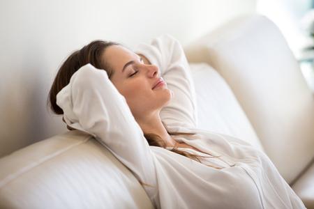 Tranquila mujer milenaria relajándose en un cómodo sofá suave meditando o tomando una siesta durante el día, despreocupada chica perezosa respirando aire fresco disfrutando de la tranquila mañana de fin de semana sin estrés descansando en el sofá