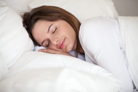 Young woman peacefully sleeping well resting on soft orthopedic pillow in comfortable cozy bed with luxury linen, healthy girl lying asleep on white sheets resting at home or hotel enjoying good nap Stockfoto