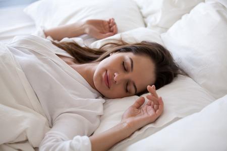 Schlafende Frau genießt ein gesundes Nickerchen in einem gemütlichen Bett am Morgen, ein tausendjähriges Mädchen, das sich auf einem weichen Kissen und einer bequemen Matratze mit weißen Baumwolltüchern entspannt, die gut schlafen und genug Ruhekonzept haben