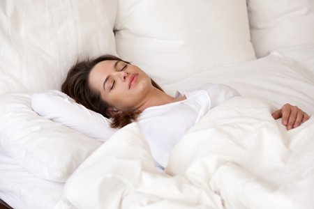Young woman sleeping well in cozy comfortable bed on orthopedic mattress pillows with cotton luxury linen covering with soft duvet resting lying asleep on white sheets enjoying healthy good sleep. Stok Fotoğraf - 107344326