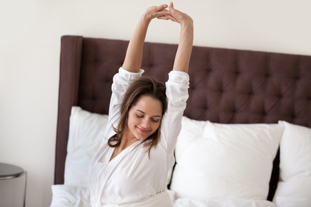 Happy smiling millennial woman awaking stretching in comfortable bed waking up early in the morning after good sleep enjoying pleasant weekend morning feeling fresh rested starting new day concept.