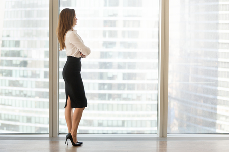 Successful businesswoman standing looking out of window enjoying city view and contemplating, confident rich woman leader thinking of business success and future vision planning new goals, copy space 免版税图像