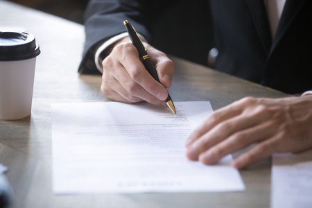 Close up man hands on the table, the man signing the contract. Lease agreement, successful deal, buy sell real estate concept