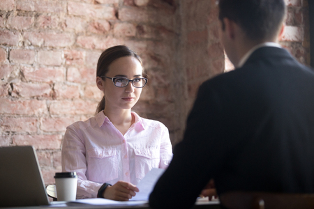 Serious young HR manager woman holding in hands curriculum vitae paper, interviewing male candidate in the office, man sitting his back to camera.