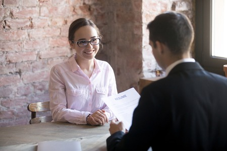 HR manager interviewing young smiling woman student in the office. Male wearing suit holding curriculum vitae sitting. Positive atmosphere, successfully passing the interview, confident girl Stock Photo
