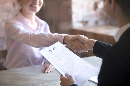 Smiling young woman and man handshake. Businesspeople shaking hands. Human resources, successfully passing the interview, hr concept. Close up resume paper Stock Photo
