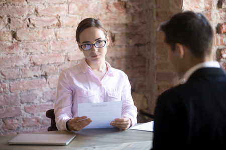 Serious HR young manager woman interviewing male in the office. Suspicious female holding curriculum vitae and looking at candidate, man sitting back to camera. Bad first Impression, failed interview Фото со стока - 107523105