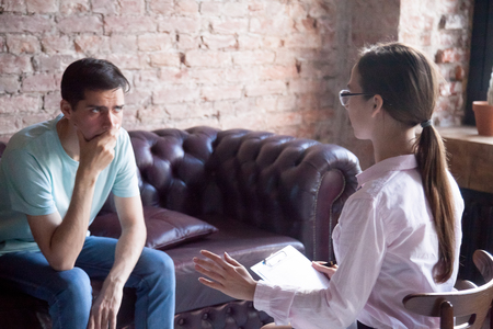 Young male visiting psychologist therapist counselor, doctor. Client looking upset, listening doctor talking. Psychological health problems, depression, drugs, disease, people need assistance concept