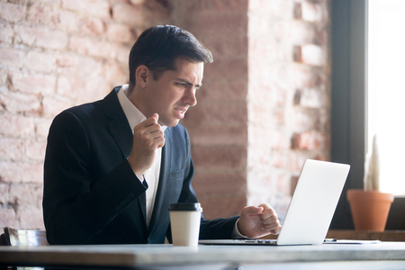 Perplexed man having problem, bad news at office work. Male looking at laptop screen. Indecision insecurity in making decision, stressed, noticed the error, failed to work, failure in business concept Stock Photo