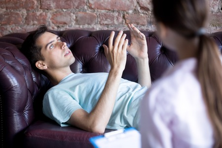 Young man at the psychotherapist, lying on couch, emotionally speaking, client discussing with female psychotherapist counselor his melancholy, mental health problems Stock Photo