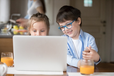 Cute happy kids watch online cartoons on laptop having breakfast at home, smiling brother and sister using computer in kitchen, curious small children addicted to gadgets busy playing on device Banque d'images - 107668198
