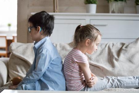 Obrażone małe rodzeństwo siada na kanapie tyłem do siebie zdenerwowani po kłótni, brat i siostra nie rozmawiają ze sobą po kłótni, mały chłopiec i dziewczynka ignorują się nawzajem bez kompromisów. Koncepcja rywalizacji