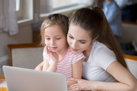 Smiling young mom hug cute little daughter watching cartoon at laptop together, happy parent spend time with kid playing game on computer, caring mother embrace girl enjoying video animation